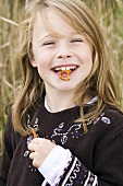 Smiling girl with salted pretzel in her mouth