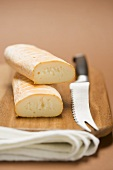 Cow's milk cheese and cheese knife on chopping board