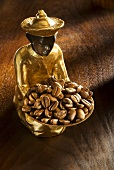 Gilded statuette with a bowl of coffee beans