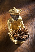 Gilded statuette with a bowl of star anise