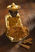 Gilded statuette with bowl of ground cinnamon, cinnamon bark