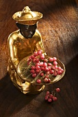 Gilded statuette with a bowl of pink pepper