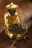 Gilded statuette with a bowl of black pepper