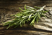 A sprig of rosemary on a wooden background