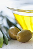 A small glass bowl of olive oil and olives