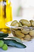 A bowl of pickled olives, olive oil, fresh olives