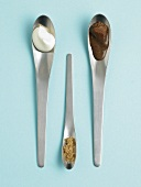 Chocolate sauce, cream and sugar on spoons (overhead view)