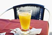 A glass of orange juice on a café table
