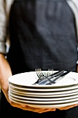 Person holding pile of plates with cutlery