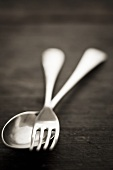 Silver spoon and fork on wooden background