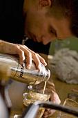 Junger Mann mixt einen Kaffee-Drink
