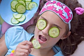 Girl with cucumber slices on her eyes eating slice of cucumber