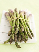 Bundle of green asparagus on tea towel