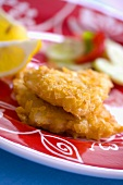 Breaded fish fillets with lemon wedges