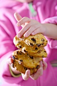 Child's hands holding raisin biscuits