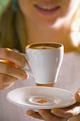 Woman holding a cup of espresso macchiato