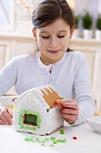 Girl decorating a gingerbread house for Christmas