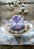Purple Easter egg with bow and sugar eggs
