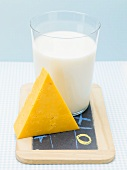 Glass of milk and piece of Cheddar cheese on slate board