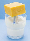 Cheddar cheese on a glass of milk
