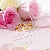 Hochzeitsmenükarte, Trauringe und rosa Rosen