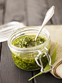 Ramsons (wild garlic) pesto in preserving jar with spoon