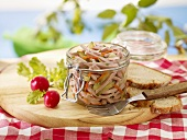 Sausage salad in a preserving jar with bread and radishes