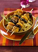 Pork and dried fruit kebabs on couscous