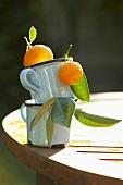 Ornamental oranges in two mugs