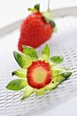 Erdbeere und abgeschnittenes Grün auf einem Gitter