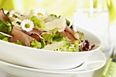 Spring salad with prosciutto, Parmesan and daisies