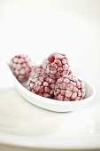 Sugared raspberries on white spoon