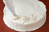 Decorating a cake (piping cream rosettes)