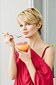 Young woman eating grapefruit with spoon