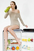 Young woman drinking fruit juice sitting on a refrigerator