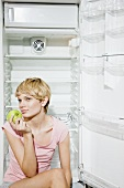 Young woman eating an apple in front of empty refrigerator