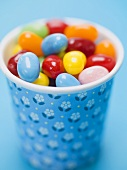 Coloured jelly beans in a beaker