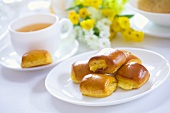 Pastries and a cup of tea on table with spring flowers