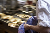 Waiter carrying plates of food in a professional kitchen