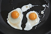 Two fried quails' eggs in frying pan (overhead view)