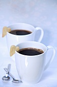 Two cups of black coffee with heart-shaped biscuits
