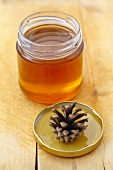 Pine honey in jar with pine cone