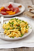 Scrambled egg with spring onions, tomatoes and bread