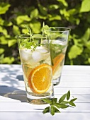 Drinks with lemon verbena and orange slices on table