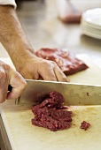 Cutting veal into small pieces (for carne cruda)
