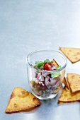 Ceviche with coriander in a glass, with bread chips