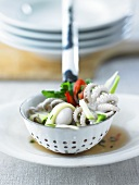 Octopus and vegetables in slotted ladle