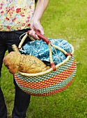 Person carrying picnic basket containing bread and wine