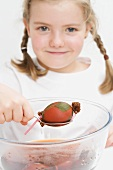 Little girl dyeing Easter eggs