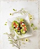 Avocadosalat mit Tomaten und Käse in zwei Avocadohälften
